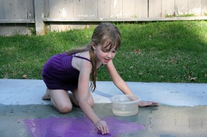 Amara gets the chalk and driveway wet to color