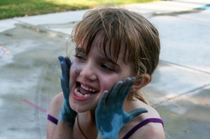 Smearing blue chalk on her cheeks
