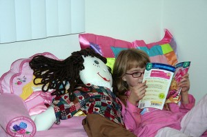 Amara likes reading books to her new doll Emily.