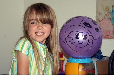Amara drew a Ladybug face on a purple balloon.