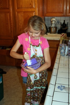 Amara mixing purple frosting