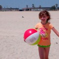 Amara arrives at the beach with her beach ball and her boogie board