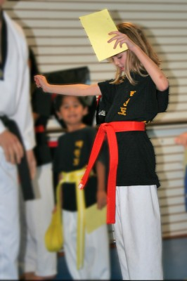 Amara receiving her orange belt