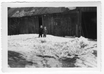 Posing the the snow in front of the old barn 1954