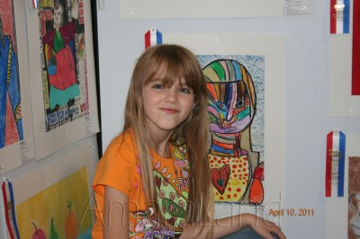 Amara in front of her artwork at the fair