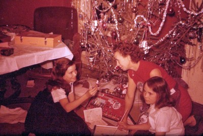 Kc and Judy with their mom and their presents next to the Christmas tree