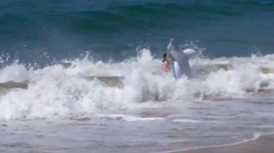 Amara and her inflated dolphin being hit by a wave